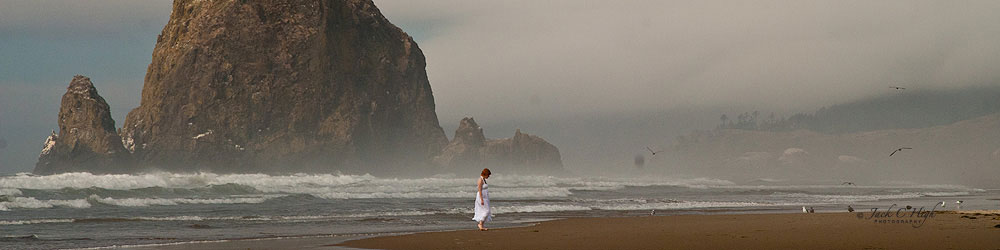 Woman in white dress walking on Cannon Beach in soltitude